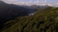 wood forest mountain valley in summer sunny sunset or sunrise dawn or dusk 4k aerial drone pan flight wide nature establishing shot video