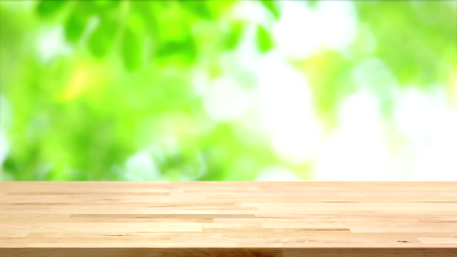 Wood table top on blur moving green leaf background video