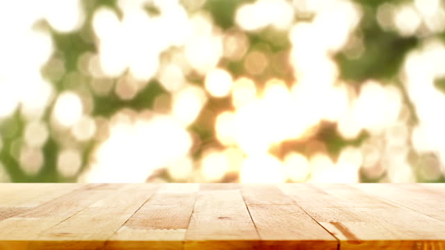 Wood table top on bright twinkled gold bokeh background video