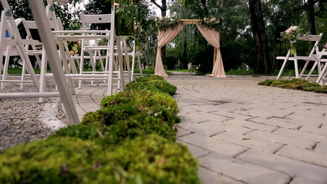 Wooden arch with curtains, flowers for ceremony on wedding day video