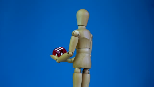 Wooden artist drawing manikin holding red game lucky dice and rotating video