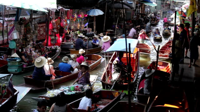 Wooden boats busy ferrying people at Damnoen Saduak Floating Market video