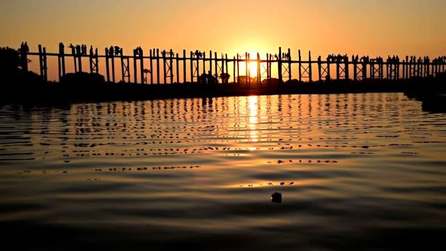 wooden bridge with pedestrians at sunset in Myanmar video