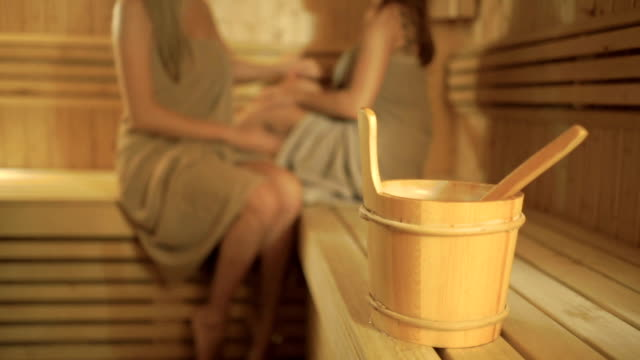 A wooden bucket with spoon on blurred background with girls relaxing in sauna video