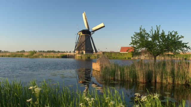 Wooden cradle floating on the river with beautiful windmill in background video