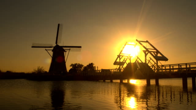 Wooden drawbridge on river with traditional windmill in background at sunset video