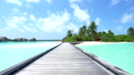 Wooden jetty leading from water villas to the beach in Maldives video