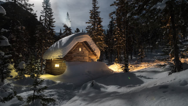 Wooden lodge with lightning windows in winter forest. video