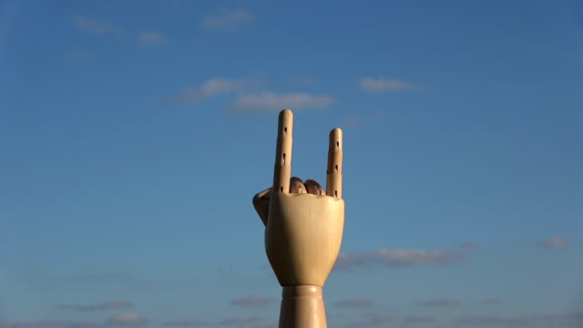 Wooden  manikin hand rotating on sky background video