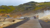 wooden runway in geothermal area Seltun in Iceland in rainy weather, tourists are walking video