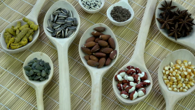 Wooden spoons with various vegetables, spice and nuts, rotating video