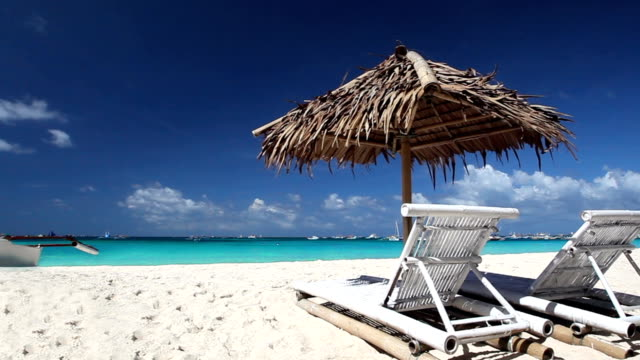 Wooden sun umbrella and two beds on tropical beach video