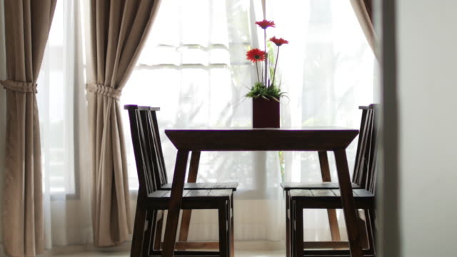 Wooden table with flower vase blur curtain window with green garden , dolly shot right to left video