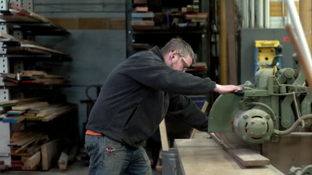 Woodworker cutting a board, slow motion video