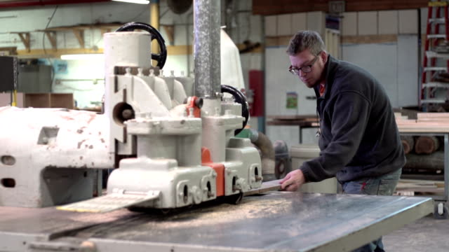 Woodworker putting board through a planer video