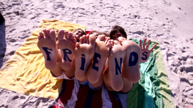 Word friends on the feet of young women lying at the beach video