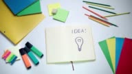 Word Idea and light bulb written on white note pad video