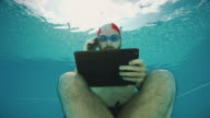 Workaholic man underwater with mobile and tablet video