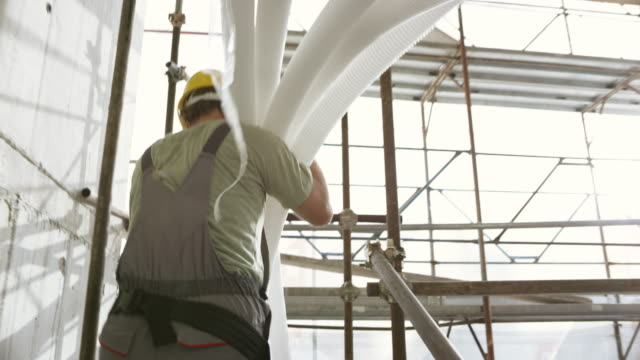Worker carrying corrugated plastic pipes up the scaffold staircase at the construction site video