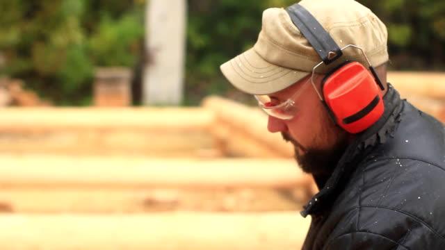 worker chainsaw sawdust video