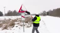 Worker cleaning warning sign from snow near road video