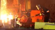 Worker cuts fiery steel blocks video