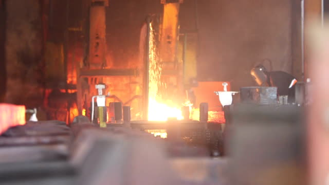 Worker cuts fiery steel blocks video