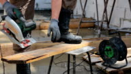 Worker cuts the board with a circular saw. video