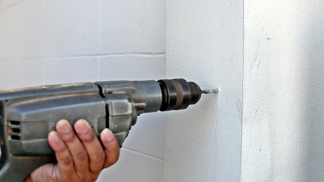 Worker drilling into wall video
