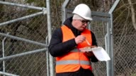 Worker eating near wire fence video