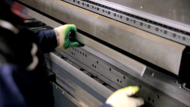 Worker hands bend metal sheet on a modern bending industrial machine at a factory video