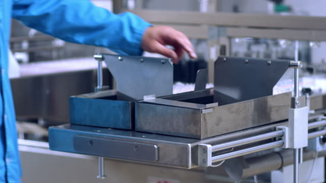 Worker hands working with pharmaceutical packaging machine video