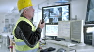 DS worker in control center updating coworkers by handheld receiver video