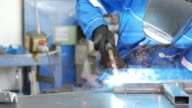 Worker in factory welding with welding torch video