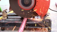 Worker in gloves cutting a metal pipe pieces with angle grinder at outdoor video