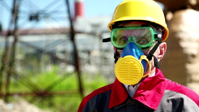 Worker in hard hat, goggles and respirator at power station video