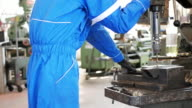 Worker in protective suit working in factory on machinery video