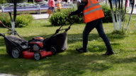 Worker in uniform mowing grass with lawn mower video