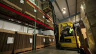 Worker in warehouse moves inventory with forklift video