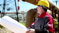 Worker in yellow hard hat with design drawings at heat station video