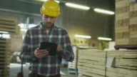 Worker is using a tablet computer in lumber factory warehouse. video