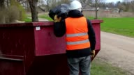 Worker keeps garbage bag on waste container and talking video