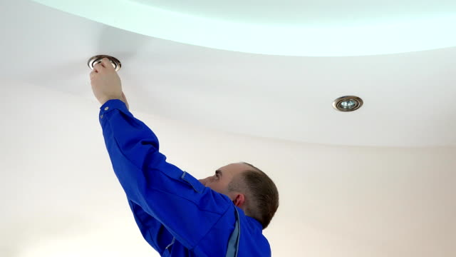 worker man install or replace halogen light lamp into ceiling video