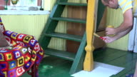 worker man paint wooden column with brush in own home room. FullHD video