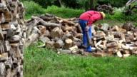 worker man split log near wood pile in garden at summertime. FullHD video