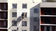 Worker man spray thermal paint on flat apartment house wall video