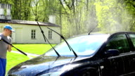 Worker man with high pressure water jet tool washing his car automobile. video