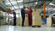 Worker moving consignment with pallet jack in a warehouse video