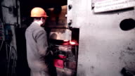 Worker operates with automated Metalworking machine at a metal forging factory video