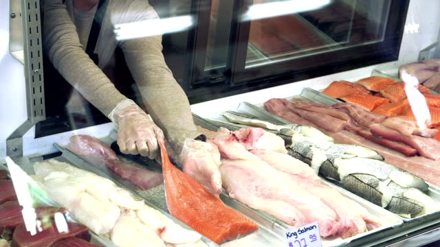 Worker reaching into fish market display case video